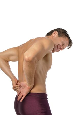 Topless athletic male suffering from excruciating lower back pain photo