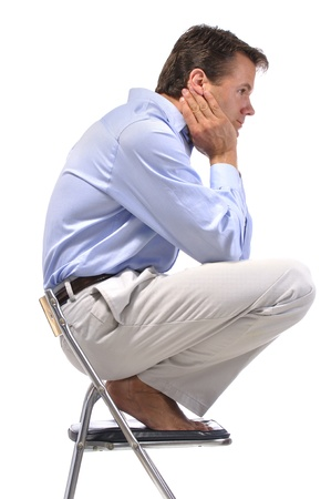 Side view of business man squatting barefoot on office chair with white background Stock Photo