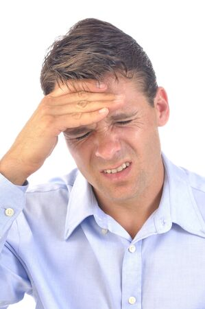 splitting headache: Closeup of business man with terrible headache as he presses his hand against forehead on white background