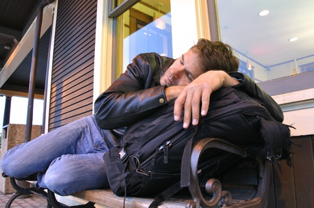journeying: Tired male traveler sleeping on bench at train station