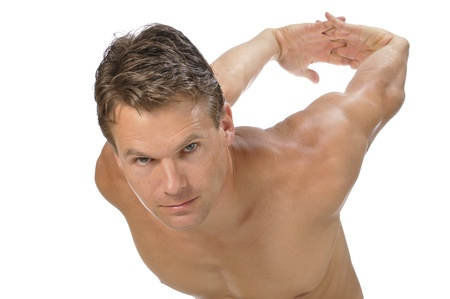Muscular athletic shirtless man stretching biceps and shoulders with arms behind back on white background photo