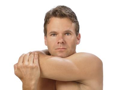 deltoids: Muscular athletic shirtless man performing rear deltoid stretch