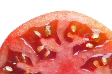 Macro closeup of half sliced tomato on white background