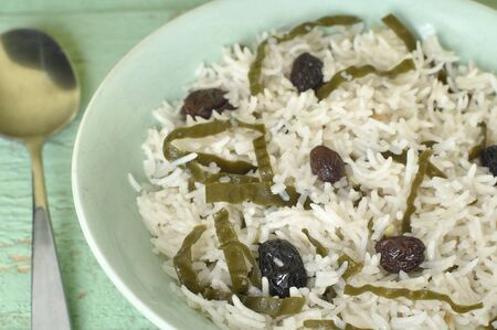 glycemic: Closeup of bowl of white rice with seaweed and raisins