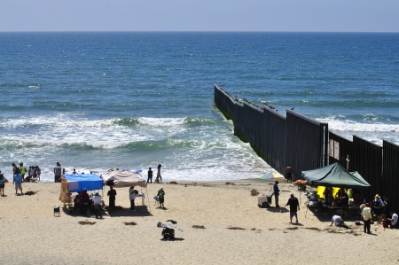 locals: TIJUANA, BC, MEXICO - JULY 28, 2012 - Locals enjoy a warm summer day at the beach on the Mexican side of the border fence separating Mexico and the United States.  This new barrier was completed early in 2012. Editorial