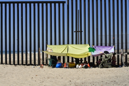 TIJUANA, BC, MEXICO - JULY 28, 2012 - Picnickers protect themselves from the summer sun by attaching sheets to the new US - Mexico border fence at the beach in Tijuana.