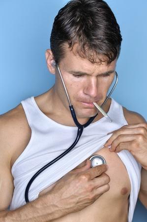 signos vitales: Hombre enfermo revisa sus propios signos vitales con el estetoscopio y el termómetro