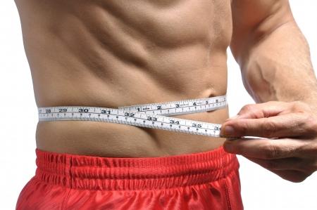 Closeup of man holding measuring tape around thin muscular waist photo
