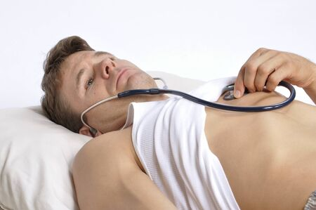 down beat: Sick man lying in bed checking his own heart with stethoscope Stock Photo