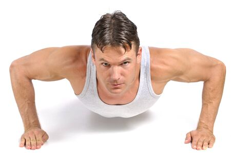 pushup: Young fit man performing pushup on white background Stock Photo