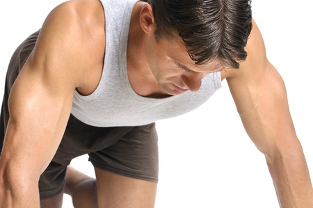 kneel down: Fit athletic man kneels and focuses to mentally prepare for workout