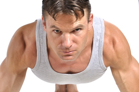 deltoids: Closeup of intense fit athletic man in pushup position on white background