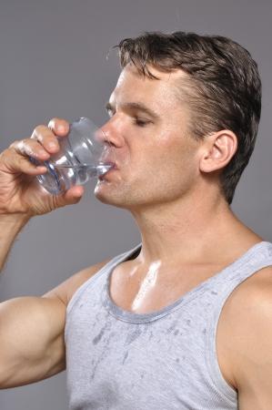 Thirsty sudoroso musculoso hombre caucásico bebidas vaso de agua Foto de archivo - 15804555