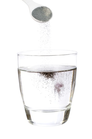 Spoonful of powdered grape soft drink mix falling into glass of water isolated on white
