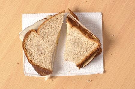 Closeup of plain lunchmeat sandwich on wheat bread on a napkin
