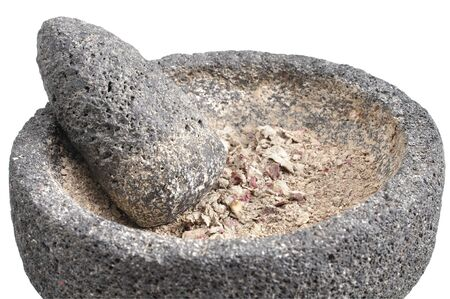 Closeup of ground potato contents of mortar and pestle on white