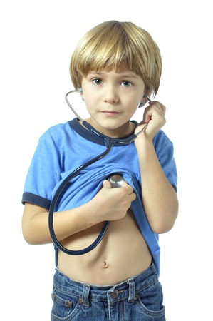 Young child longs to become a doctor as he checks his heart with a stethoscope on white background Standard-Bild