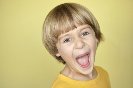 Closeup of young blonde boy screaming on yellow background Фото со стока