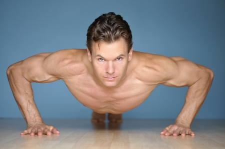 Handsome muscular man looks at camera while performing pushup on floor with blue wall background Stock Photo - 16640701
