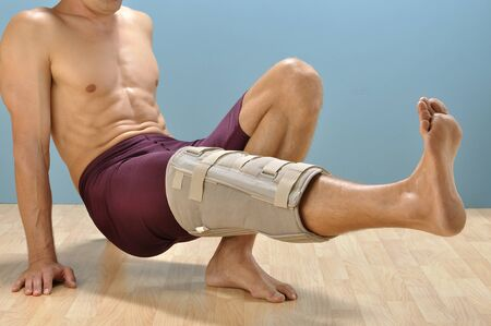Male athlete with leg injury does leg lift exercise to strengthen leg Stock Photo - 16648185