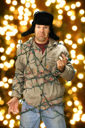 tangled: Funny confused man wrapped in colorful Christmas lights Stock Photo