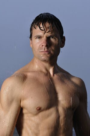 Sexy shirtless man standing in rain with stern look on face Stock Photo - 16717705