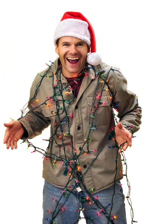 Joyful man in santa hat having fun as he gets tangled in colorful Christmas lights Stock Photo - 16717704