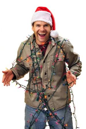 Joyful man in santa hat having fun as he gets tangled in colorful Christmas lights