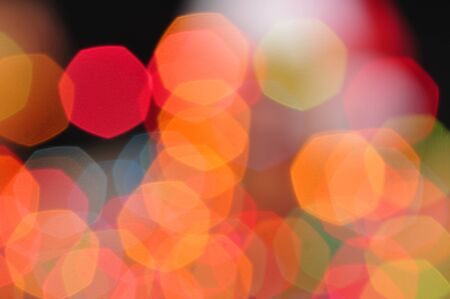 out of focus: Colorful blurred Christmas lights in orange, red, blue and green form heptagon shapes