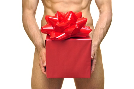 nude man: Nude man holds gift with red wrapping paper and red bow in front of pelvis area on white background