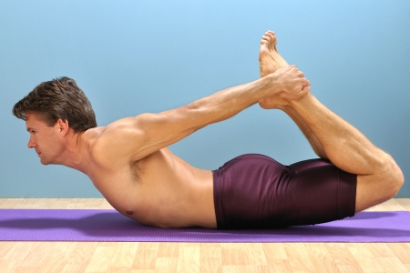 Shirtless athletic man demonstrates a yoga bow pose on mat Stock Photo - 16734473
