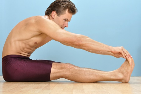 Athletic shirtless man performs sitting hamstring stretch by touching toes on wood floor Stock Photo - 16734472