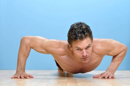 Muscular shirtless man performs modified pushup on wooden floor Stock Photo - 16734469