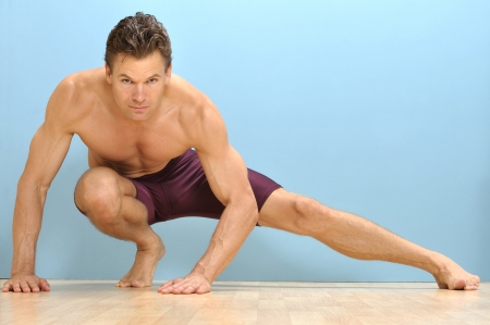 Muscular topless man performs side lunge stretch on wood floor and blue background Stock Photo - 16734471