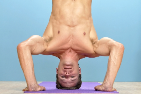Shirtless muscular man performs three-point head stand with hands on floor Stock Photo - 16734470