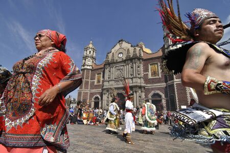 religious event: Mexico City, Mexico - December 12, 2012 - Performers dressed in traditional Aztec costumes dance in front of the basilica of Our Lady of Guadalupe in Mexico City celebrating the annual religious event on December 12, 2012. Editorial
