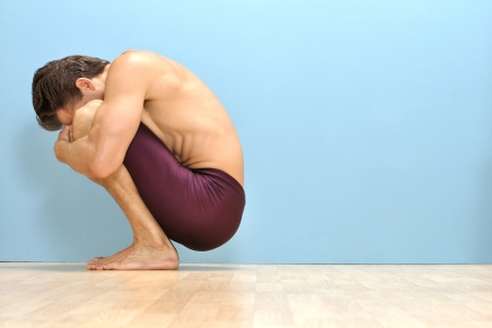 Muscular topless man squeezes himself into tight ball squat position Stock Photo - 16882311