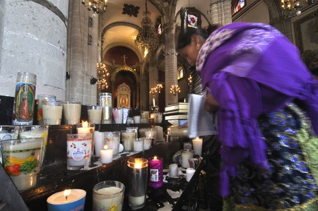 veneration: Mexico City, Mexico - December 12, 2012 - A faithful Catholic lights a candle in the old basilica of Guadalupe in veneration of the Virgin on December 12, 2012.