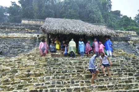 Palenque, Chiapas, Mexico - December 21, 2012: Heavy rains force visitors to seek shelter under a thatched roof next to the Temple of the Skull at the Maya ruins in Palenque, Chiapas, Mexico on December 21, 2012 Éditoriale
