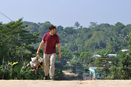 Caucasian man carries two chickens on dirt road in tropical village photo
