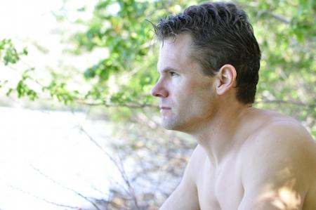 Closeup of pensive shirtless man thinking in natural surroundings photo