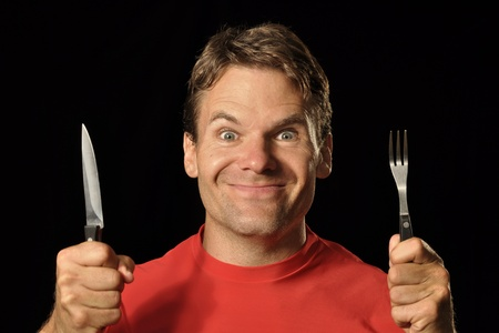 holding a knife: Closeup of hungry Caucasian man in red shirt holding knife and fork on black background while making silly face