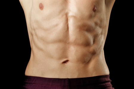 belly button: Closeup of athletic mans abs on black background