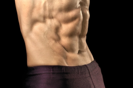 Closeup of shirtless man flexing highly defined abs on black background