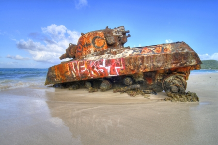 tropical tank: Old remnant tank partially sunk in sand at Flamenco Beach on the tropical island of Isla Culebra, Puerto Rico Editorial