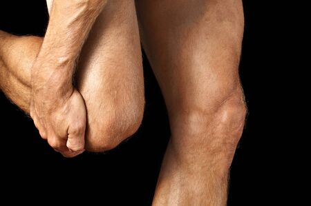 hairy legs: Closeup of man grasping his knee while walking on black background