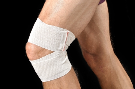 knee cap: Closeup of man with sports wrap on knee as he runs on black background