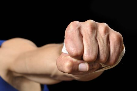 Closeup of muscular man throwing fist at camera on black background photo