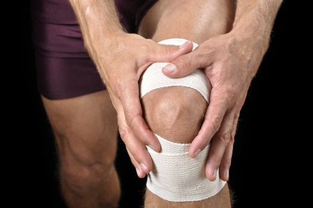 Closeup of athletic man tending wrapped injured knee on black background