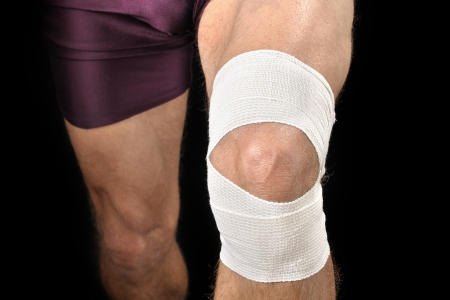 Front closeup of knee of athletic man with white sports wrap on black background